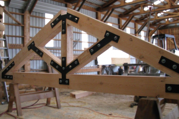 timber truss with exposed connectors on saw horses in shop