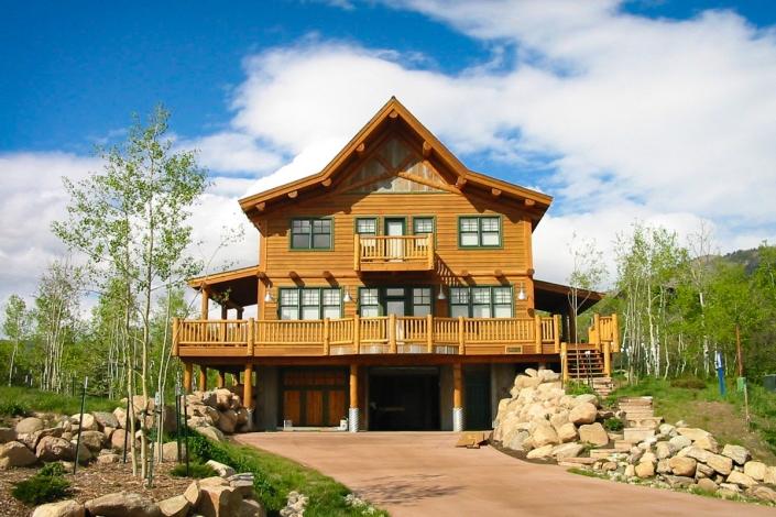 log house exterior with log railing and blue sky
