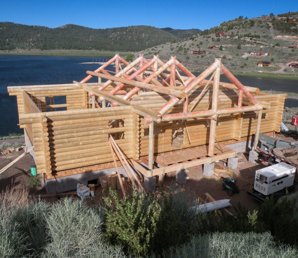 log home with log trusses showing during construction
